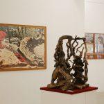 Sullo sfondo composizione a muro di Lordes De La Riva, Artificio 006. Serie The Creators, tecnica mista fotografia digitale con inchiostro su carta di cotone, 160x106 cm. 2012