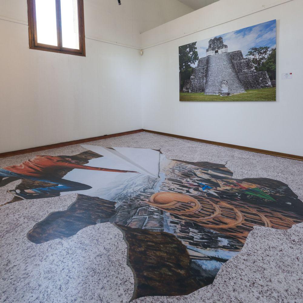 Sulla parete opera fotografica di Aldo Basili, Tempio delle Maschere di Tikal, 135x200 cm. 2017; sul pavimento installazione di Tina Marzo, Torre di Babele, anamorfismo, tecnica mista, misure variab. 2018